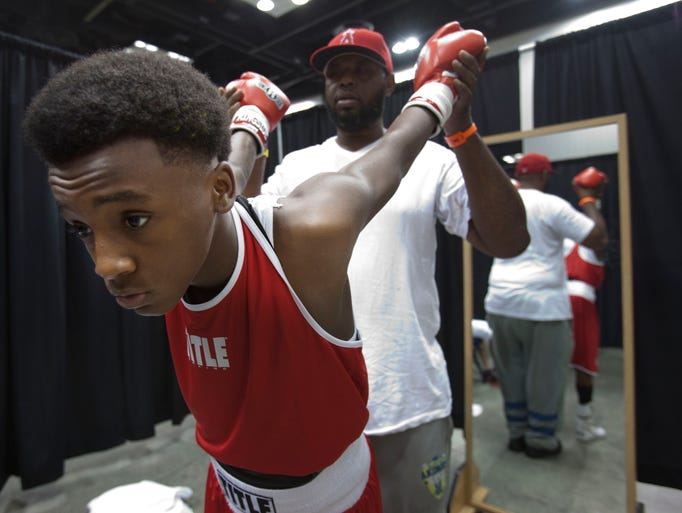 DaSean Monor, 13, of Cincinnati, gets stretched out by his coach Douglas Foggie before his fight at Indiana Black Expo Saturday, July 20, 2013.