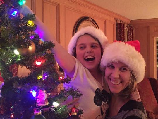 Marisa Tufaro decorates a tree with her mother, Cyndi.