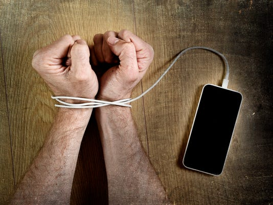 man hand wrists wrapped  with mobile phone cable handcuffed