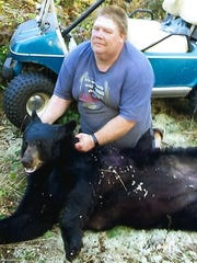 Earl Avery of Whitelaw shows the 300-pound bear he harvested in Marinette County.