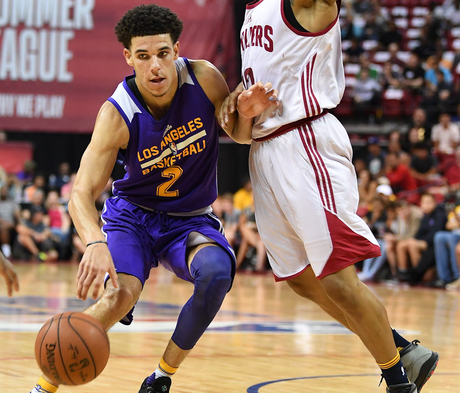 Lonzo Ball dribbles against the defense of Cleveland Cavaliers guard TJ Williams during an NBA Summer League game.