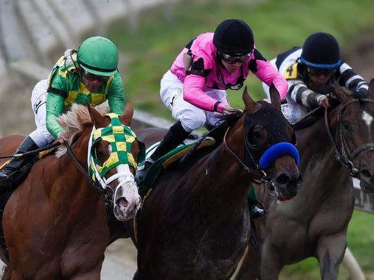 American Freedom (pink silks) pulls ahead coming out of the turn to win the Sir Barton Stakes at Pimlico.