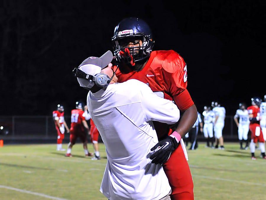 Assistant coach Cain Smith celebrates Quinton Poole's 98-yard touchdown run against Loretto.
