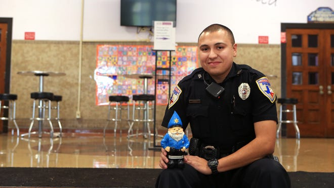 Corpus Christi Independent School District Officer Carlos Lazo sits with Officer Gnome Johnson in the lobby of Metro Elementary School of Design last month. Lazo uses the gnome as an icebreaker with students.