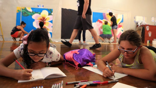 Heaven Garrison (left), 11, and Hannah Villarreal, 9, students at the K Space Contemporary summer art camp focused on mural arts, draw during free time on Friday, June 30, 2017. Students participating in the camp are painting and installing a mural in a parking garage downtown. The one-week camp will be held five times this summer. Each week a portion of the mural will be installed.