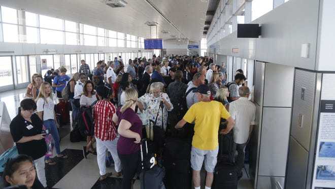 People pack the Sky Train entrance in Terminal 3 on their way to Terminal 4 after its closure at Sky Harbor Airport in Phoenix on Sept. 16, 2018.