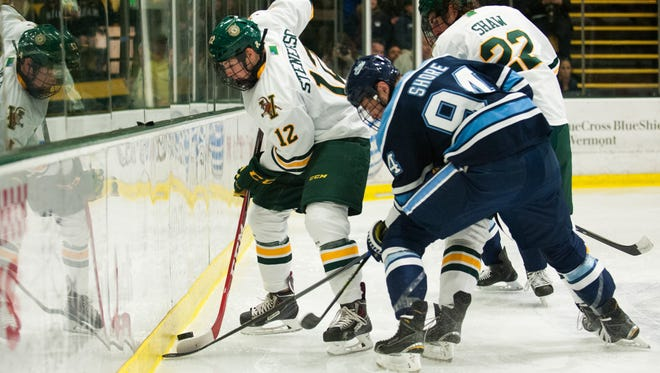 Vermont forward Mike Stenerson (12) battles for the puck along the boards during Friday night's hockey game against Maine at Gutterson Fieldhouse.