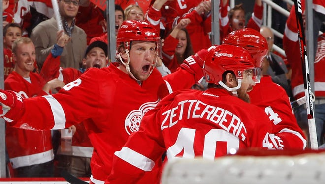 Red Wings forward Justin Abdelkader, left, celebrates his second goal of the first period with Henrik Zetterberg and Jakub Kindl during the 4-0 win Friday at Joe Louis Arena.