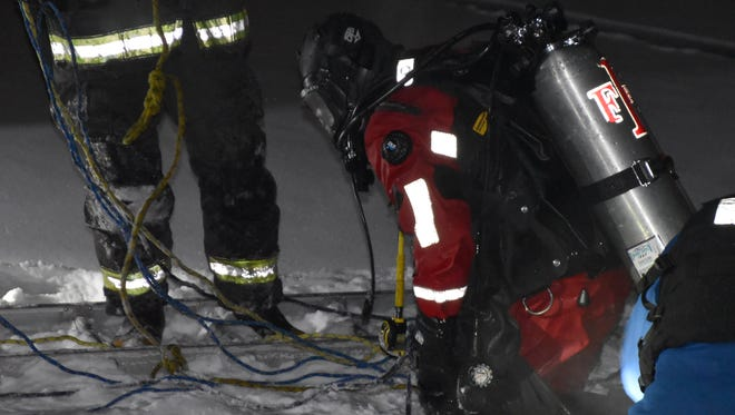 IFD crewmembers work to remove a woman from her car after it plunged into an icy retention pond on New Year's Eve 2017.