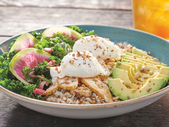 Ancient Grains Protein Bowl from First Watch made with quinoa, farro and brown rice topped with two poached eggs, chicken, avocado, lemon white balsamic vinaigrette and super seed crunch served with kale, watermelon radish and pickled onion salad.