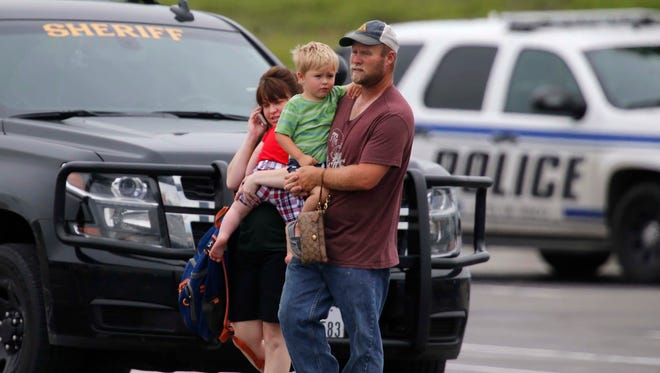"""People leave a restaurant next to a Twin Peaks restaurant Sunday in Waco, Texas. Waco Police Sgt. W. Patrick Swanton told KWTX-TV there were """"multiple victims"""" after gunfire erupted between rival biker gangs near the restaurants."""
