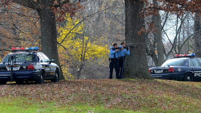 Lansing Police officers surround a wooded area by Cavanaugh Park Thursday as they look for a suspect wanted in connection with the break-in of a home that resulted in an exchange of gunfire with the resident.