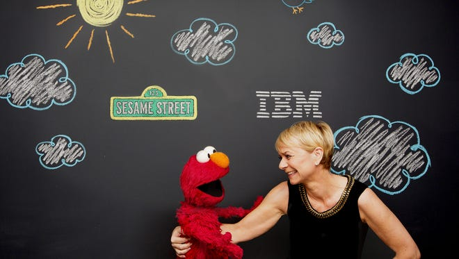 """IBM's Harriet Green poses with Sesame Street's Elmo. IBM and Sesame Workshop are announcing a three-year partnership to use the power of the Watson supercomputer to develop educational tools for preschoolers. (Photo: John O""""Boyle)"""