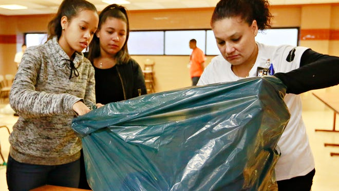 From left, William Penn Senior High School seniors Yeniffer Jose, 17, and Fraberlin Raynoso, 16, open a bag of clothing while working with bilingual teaching assistant Madeline Skinner during York City Cares ... A Resource Fair at the high school in York City, Saturday, Dec. 9, 2017. Dawn J. Sagert photo