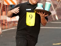 Cerina Soto of Chili's Bar and Grill places first in the mascot race during 22nd annual Waiters Race on Main Street in downtown Visalia on Thursday.