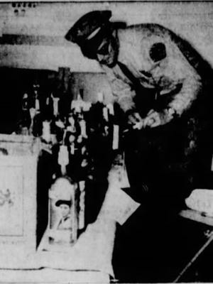 LOOKING OVER LOOT-City Police Sgt. Harry Wiseman views some of the 40 bottles of whiskey recovered from the breakin of Stinnett's Bar early this morning. The burglars apparently were interrupted in their looting of the bar by Wiseman and capt. Rex Carrell, who recovered the liquor from the rear of the building and across the railroad tracks behind it. Also recovered was a quantity of meat taken from the A& W Root Beer stand.