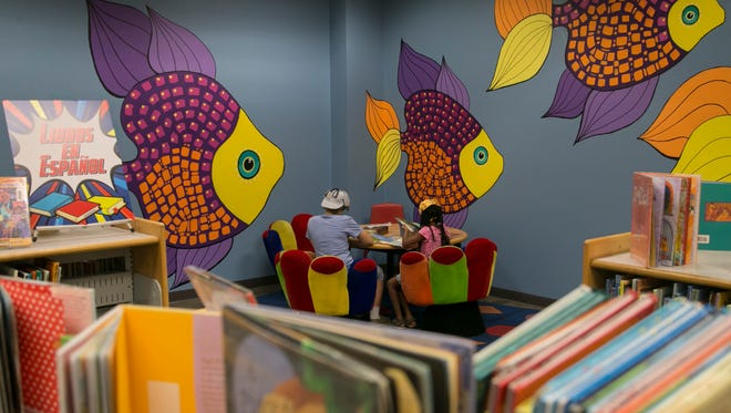 Children read through books in front of a mural inside the Mesa Library on Monday, August 11, 2014.