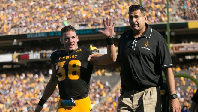 ASU safety Jordan Simone waves to the crowd after returning the field after he went into the locker room for an injury during the second quarter of the college football game against Washington at Sun Devil Stadium in Tempe on Saturday, November 14, 2015.