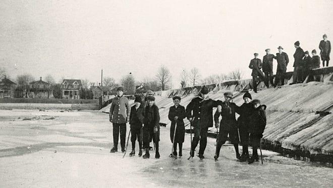 Boys play hockey on the Fox River next to the Neenah dam, circa 1910s.