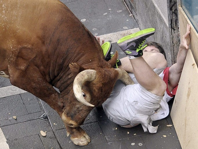 A bull gores a runner, on July 14, during the eighth bull run at the San Fermin fiesta  in Pamplona, Spain. Two runners were gored and another five injured after being knocked over during the last race of the nine-day long running-with-the-bulls.