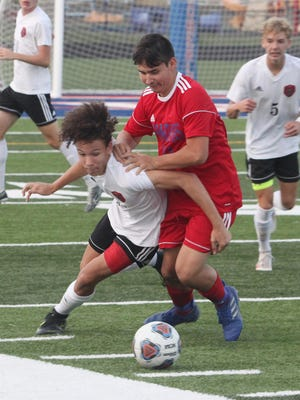 Moberly junior Chris Coonce (red shirt) engages with Hannibal sophomore DawShon Glasgow for possession of the soccer ball during the first half of Tuesday's home game. Coonce netted the go-ahead goal in the second half to help the Spartans secure a 2-1 victory.