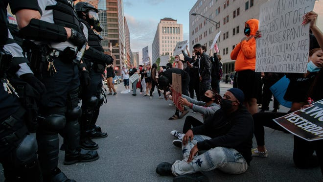 """Protesters sit in the middle of Broad and Front streets as Columbus Division of Police officers stand nearby during nationwide protests following the death of George Floyd on Friday, May 29, 2020 in Columbus, Ohio. Floyd, 46-year-old black man, died while in police custody earlier this week in Minneapolis after allegedly passing a counterfeit $20 bill at a convenience store. Minneapolis police officer Derek Chauvin, who was one of four police officers involved in Floyd's arrest, has himself been arrested and charged with third-degree murder and manslaughter. Video footage showed Chauvin kneeling down on Floyd's neck for just over nine minutes during the arrest as Floyd repeatedly said """"I can't breathe."""""""