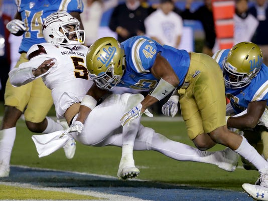 Arizona State quarterback Manny Wilkins, left, scores past UCLA linebacker Kenny Young during the first half of an NCAA college football game in Pasadena, Calif., Saturday, Nov. 11, 2017. (AP Photo/Chris Carlson)