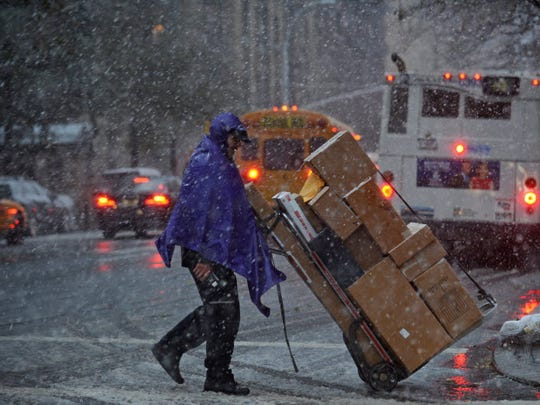 A man makes deliveries while snow falls on Madison