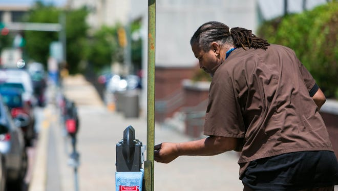 SUCHAT PEDERSON/THE NEWS JOURNAL A man feeds the parking meter along North French Street in Wilmington. A man feeds the parking meter along North French Street in Wilmington.