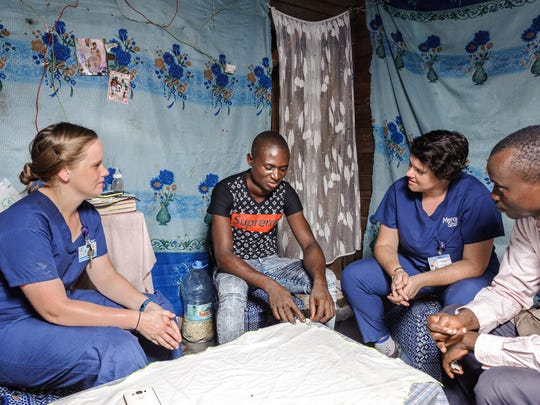 Palliative care team, including nurse Jenni Nelson on the left, visits patient Olivier at his place.
