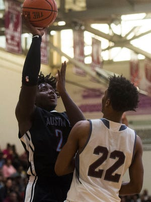 Austin-East's Chris Hunter (24) takes a shot while defended by Fulton's Josh Berry (22) during a game between Fulton and Austin-East at Fulton High School Saturday, Jan. 6, 2018. Fulton defeated Austin-East 73-51.