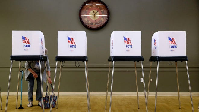A woman places her purse at her feet as she prepares to vote at a polling place in Silver Spring, Maryland in June.