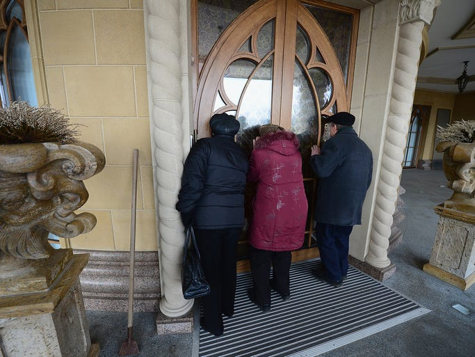 People peek into the home of former Ukranian president Viktor Yanukovych on Feb. 26 in Kiev. The leader's Mezhyhirya estate was abandoned by security personnel after he was ousted by parliament.