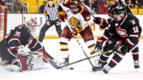 Kyle Osterberg (8) of Minnesota Duluth shoots the puck on goal on St. Cloud State goaltender Charlie Lindgren during Friday's game at Amsoil Arena in Duluth. Minnesota Duluth defeated St. Cloud State 4-2.