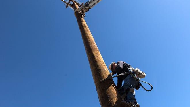 Eddie Quintana a journeyman lineman with Farmington Electric Utility System, climbs down an Osprey platform on Thursday at Navajo Dam.
