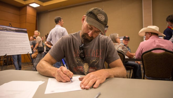 San Juan Mine underground miner John Huttinga fills out a comment form Thursday during a scoping meeting at the Farmington Civic Center.