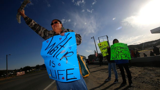 Dawn Dullknife-Teller holds a protest sign on Sept. 21, 2016, related to issues concerning the AV Water Co. in Crouch Mesa.