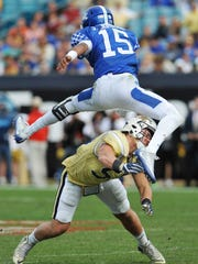 Kentucky quarterback Stephen Johnson (15) leaps over Georgia Tech linebacker Brant Mitchell (51) during the second half of the TaxSlayer Bowl NCAA college football game at EverBank Field in Jacksonville, Fla., Saturday, Dec. 31, 2016. Georgia Tech won 33-18. (Will Dickey/The Florida Times-Union via AP)