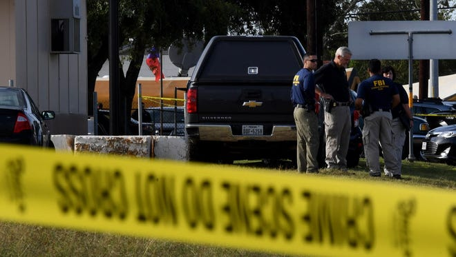 FBI agents search for clues at the entrance to the First Baptist Church, after a mass shooting that killed 26 people in Sutherland Springs, Texas on Nov. 6, 2017.