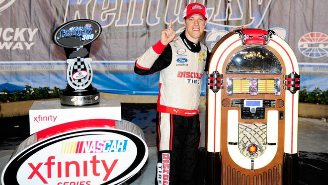 Brad Keselowski poses with his Crosley jukebox after winning Friday's Xfinity Series race at Kentucky Speedway.