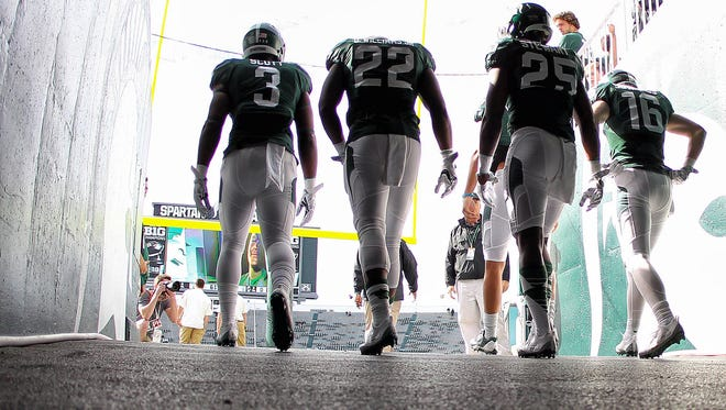 Michigan State Spartans players enter the field prior to a game against the Wisconsin Badgers at Spartan Stadium.