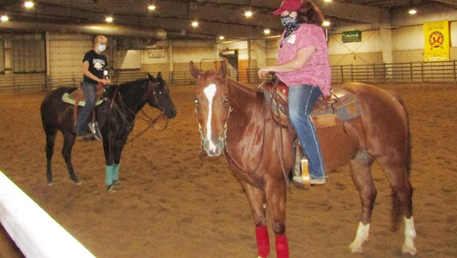 Hunter Herschelman, left, a freshman welding student from Galesburg, receives instruction from BHE equestrian science instructor Bekah Irish, both masked, during a stock equitation class in the Ag Arena, which easily allows for social distancing due to its size. Herschelman is a member of BHE's horse show team.