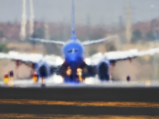 A Southwest Airlines 737 appears as a mirage from heat rising from the runway as it lands at Sky Harbor International Airport as the temperature hit 119 degrees June 20, the hottest day of 2017.