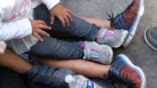 A Mexican woman and a child sit at the summit of the Paso Del Norte Bridge while they wait for word on their asylum request June 20. They were eventually escorted into the port of entry facility.