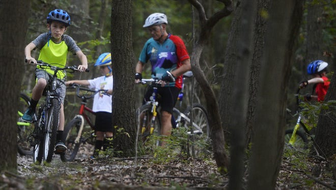 Braden Crone, 12, of Shiloh, finds a path around a big log on the path at Rocky Ridge County Park in Springettsbury Township during the first kids group mountain bike ride in September 2016. The ride was popular, but leaders said the kids struggled with some obstacles to big for their little tires.
