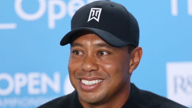 Tiger Woods of the US smiles during a press conference ahead of the British Open Golf championship at the Royal Liverpool golf club, Hoylake, England, Tuesday July 15, 2014. The British Open starts on Thursday July 17. (AP Photo/Peter Morrison)