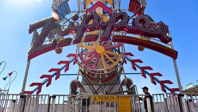 Jason Potter, of James E. Strates Shows of Orlando, inspects the Zipper ride after its assembly Thursday in preparation of the opening of the Firefighters' Indian River County Fair Friday.