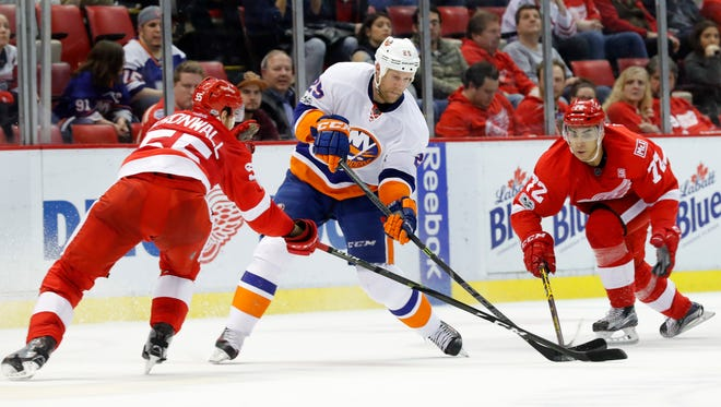New York Islanders left wing Jason Chimera (25) tries to shoot as Detroit Red Wings defenseman Niklas Kronwall (55) and Detroit Red Wings center Andreas Athanasiou (72) defend during Tuesday's game.