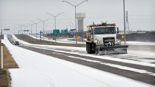 TORIN HALSEY/TIMES RECORD NEWS    A Texas Department of Transportation snowplow clears a lane of the Kell Freeway