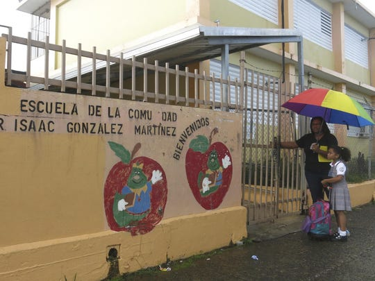 In this May 5, 2017 file photo, Ana Sanchez and her 8-year-old daughter Naiyari lock the gates of her school, The Dr. Isaac Gonzalez Martinez school, one of 179 closing that month amid an economic crisis in San Juan, Puerto Rico.